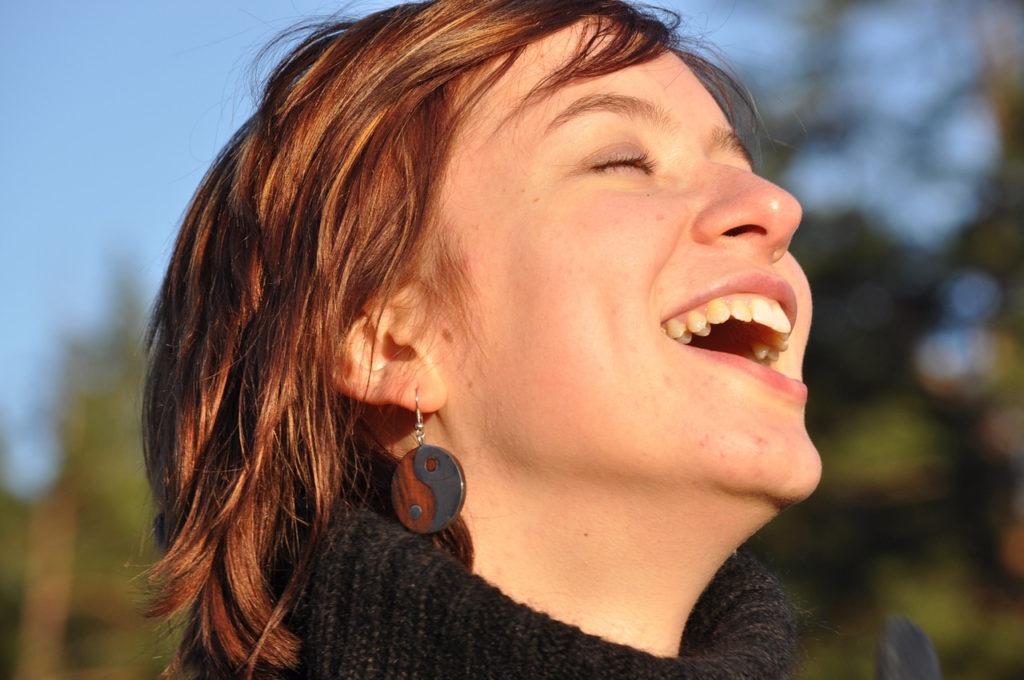 femme souriante, visage exposé à la lumière naturelle